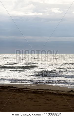 Photo closeup of beautiful clear grey sea ocean water waves hit seashore wet beige sand with splashes spindrifts spoondrifts in dull murky day over seascape background vertical picture stock photo