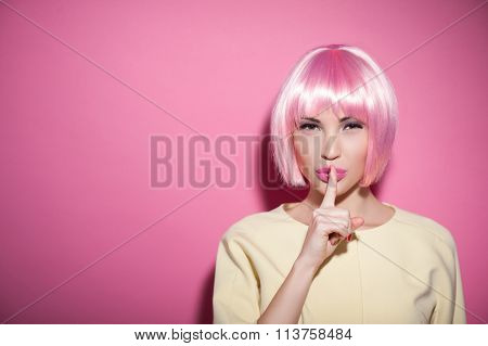 Save my secret. Portrait of attractive woman in a wig raising finger to her pink lips. She is standing and looking at camera mysteriously. Isolated and copy space in left side stock photo