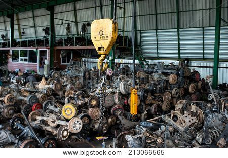 The recycle garage sale about old car wheel axles and used parts of car photo with indoor low and dark lighting. stock photo