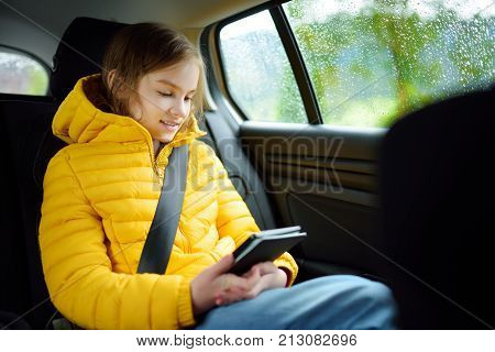 Adorable girl sitting in a car and reading her ebook on rainy autumn day. Child entertaining herserf on a road trip. Traveling by car with kids. stock photo