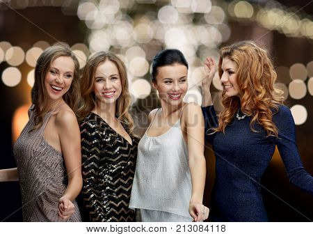 party, holidays, christmas and people concept - happy young women dancing over night lights backgrou