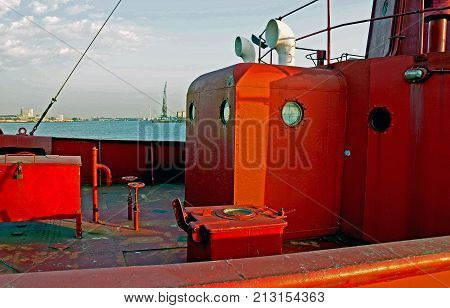 An old red lightship which has served the seas for over a century rests in its harbour in the afternoon sun. It sharply shows hinges, nuts , bolts, steel plates, welded repairs, rust and the infuence of time. The background is \'romantically\' blurred but s