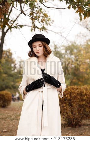 Retro gangster girl in black hat and fur coat in autumn park against a background of yellow trees looking down. Retro. On open air. stock photo