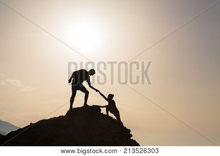 Teamwork couple helping hand trust silhouette in inspiring mountains. Team of climbers assistance man and woman hiker help each other on top of mountain beautiful sunrise landscape in Crete Greece