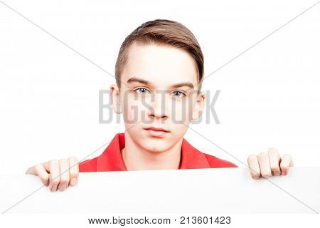 Cute teenager boy displaying blank white board or banner on white background showing no emotions stock photo