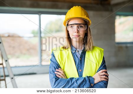 Female worker on the construction site. Beautiful young woman with crossed arms.