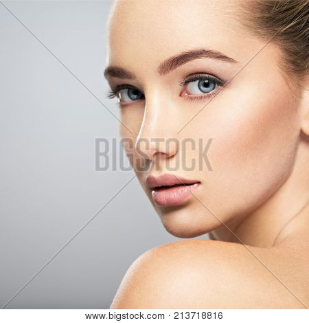 Beautiful face of young caucasian woman with perfect health clean skin.  Skin care treatment. Portra