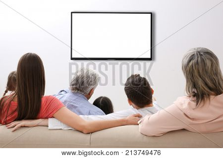 Family and blank TV display at home stock photo