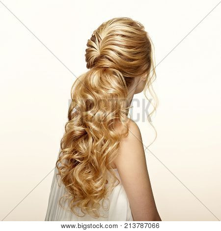 Blonde Girl with Long and shiny Curly Hair. Beautiful Model Woman with Curly Hairstyle. Care and Beauty Hair products. Care and Beauty of Hair stock photo