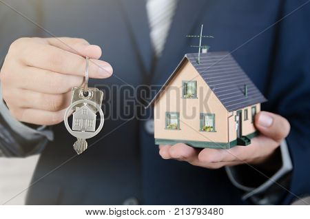 Real estate agent with home keys and house miniature. realestate key apartment real estate home house homeowner concept stock photo