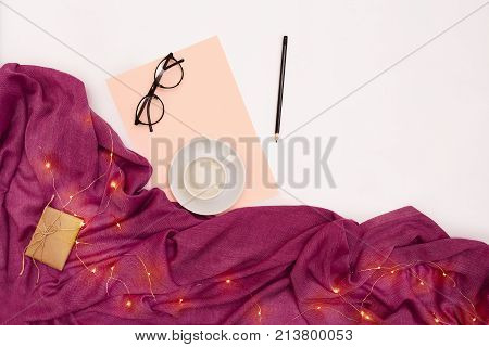 A cup of coffee, black glasses, pink paper with new years goals. Scarf and Christmas lights on white background. Top view. Copy space. Still life. Flat lay stock photo