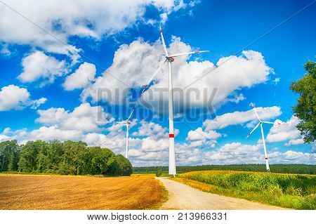 Alternative energy source. Turbines on field on cloudy blue sky. Wind farm in Lower Saxony Germany. Global warming climate change. Eco power green technology concept.