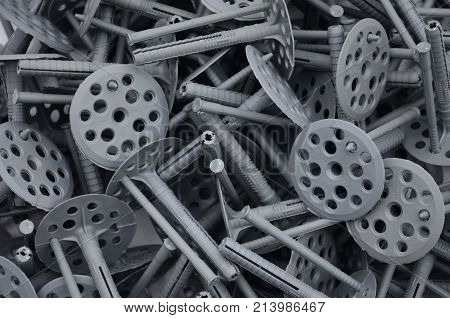Background pattern of many gray plastic dowels (fastening) for thermal insulation. A huge pile of fixtures for the installation of expanded polystyrene plates for the insulation of the building walls stock photo