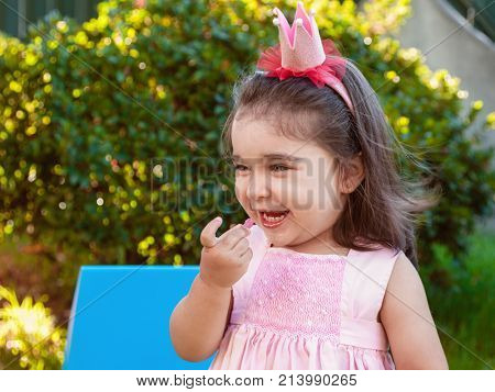 Very happy baby toddler girl, eating gummies laughing and smiling in outdoor party dressed in pink dress as princess or queen with crown stock photo