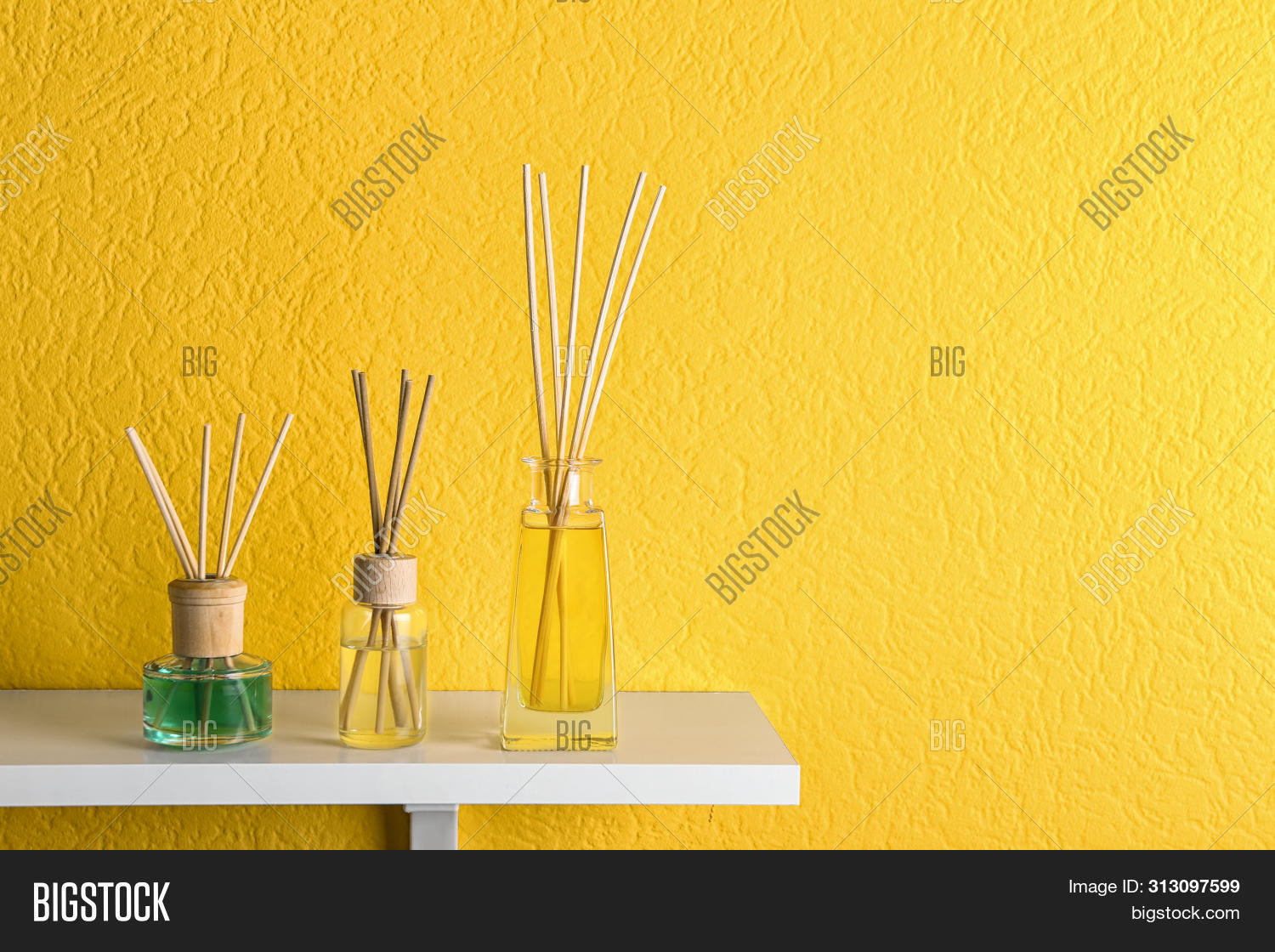 Reed air fresheners on table against yellow background, space for text