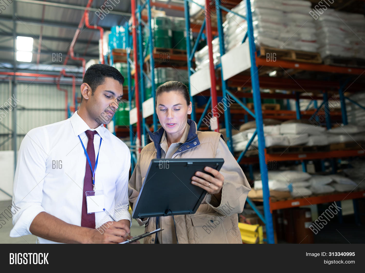 business,caucasian,caucasian ethnicity,commercial,coworker,digital tablet,distribution,distribution warehouse,expertise,factory,female,freight,freight transportation,holding,industry,interacting,inventory,logistics,looking,male,man,management,mid adult,mid adult women,mixed-race,mixed-race person,occupation,packaging,pallet rack,professional,reading,shipping,skill,staff,standing,stock,storage,storehouse,supervisor,supply,tablet computer,tablet pc,talking,uniform,warehouse,well dressed,woman,workplace,young adult,young men