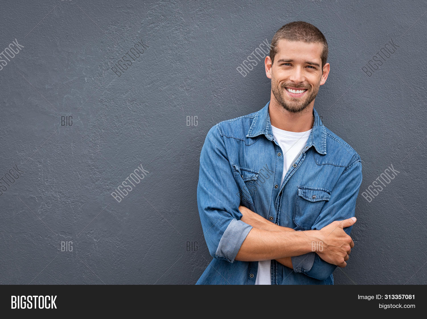 arm,background,carefree,casual,cheerful,confident,cool,cool guy,copy space,crossed,crossed arms,fashionable,friendly,gray,gray background,grey wall,guy,handsome,handsome man,happy,healthy,isolated,leaning man,looking,looking at camera,people,portrait,positive,pride,proud,satisfaction,satisfied,satisfied man,sincere,smile,standing,studio,stylish,success,successful,toothy smile,wall,young,young man