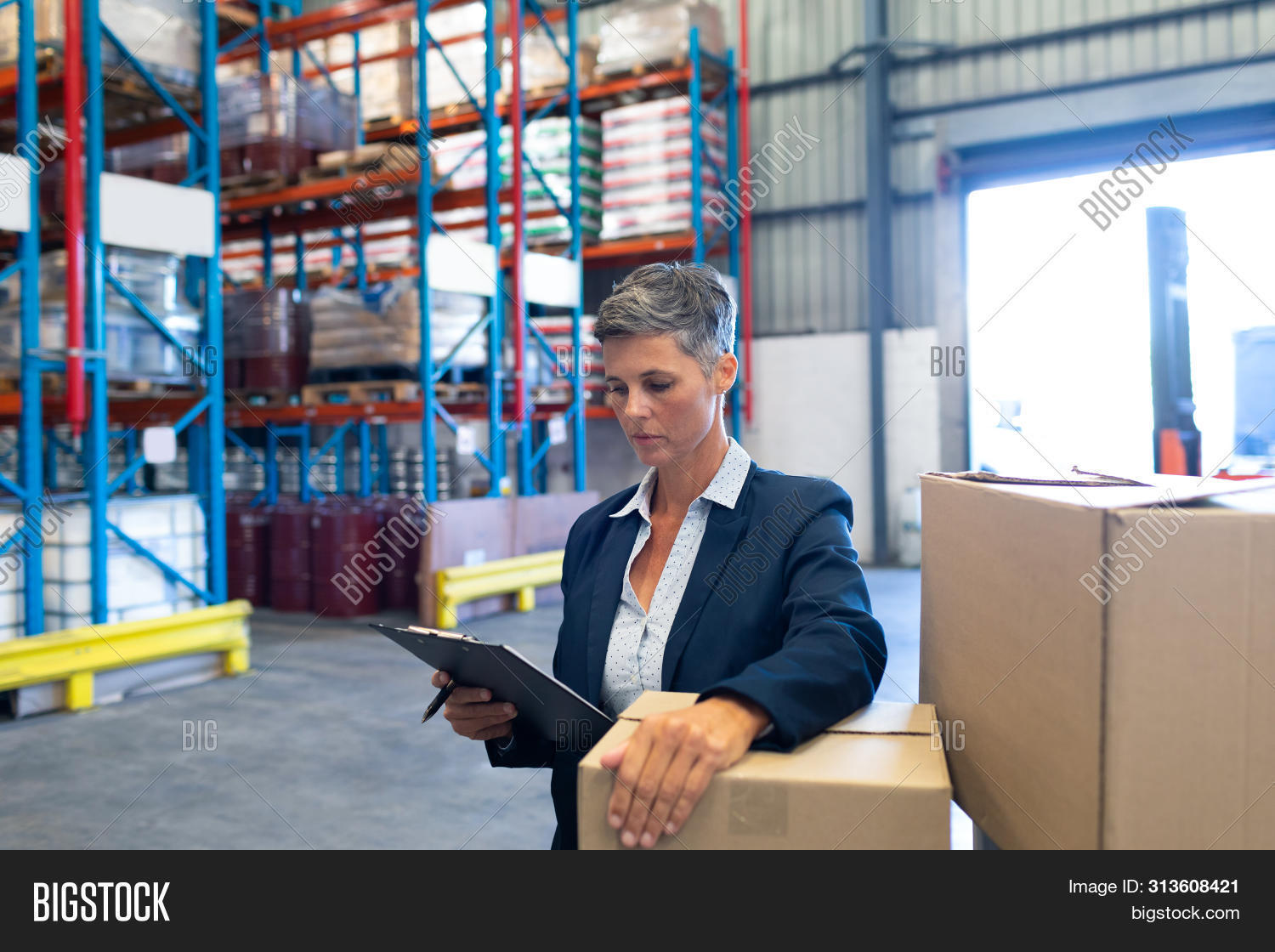 Front view of beautiful mature Caucasian female manager checking stocks on clipboard in warehouse. T