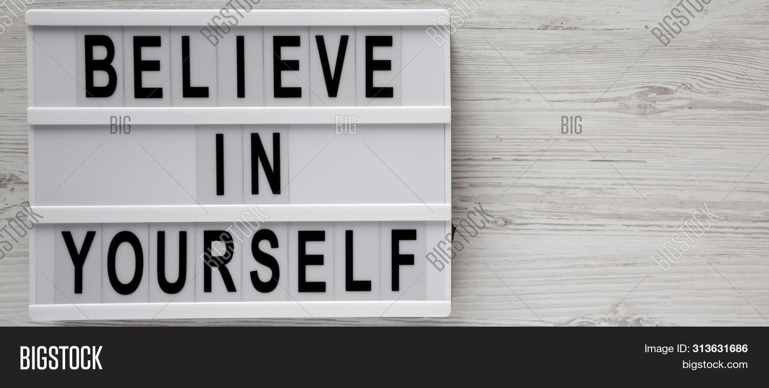 Overhead View, 'believe In Yourself' Words On A Lightbox On A White Wooden Background, Top View. Fro