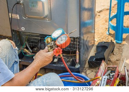 repair refrigerator job with pressure gauge , technician vacuum system refrigerator at maintenance shop. stock photo