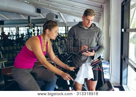 Front view of young Caucasian Male trainer assisting Caucasian female athlete with exercise in fitness studio. Bright modern gym with fit healthy people working out and training stock photo