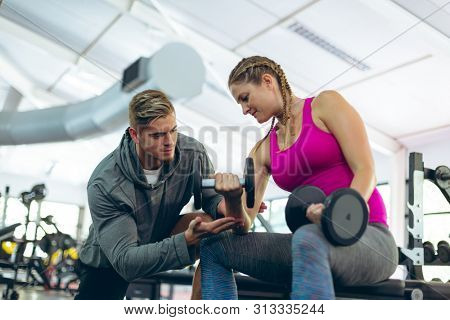 Low angle view of handsome young Caucasian male trainer assisting fit young Caucasian female athlete to exercise with dumbbells in fitness center. Bright modern gym with fit healthy people working out stock photo