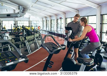 Front view of handsome Caucasian male trainer assisting pretty Caucasian female athletic to work out on exercise bike in fitness center. Bright modern gym with fit healthy people working out and stock photo