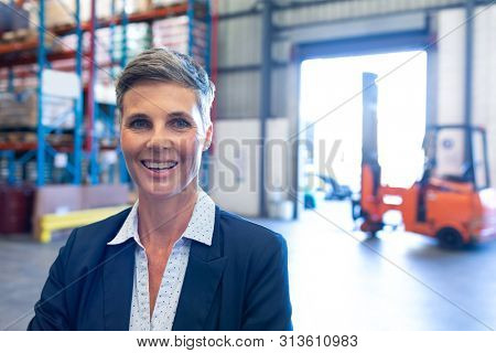 Portrait close-up of beautiful mature Caucasian female manager looking at camera in warehouse. This is a freight transportation and distribution warehouse. Industrial and industrial workers concept stock photo