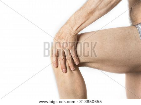 Man is holding his aching knee with a hand stock photo