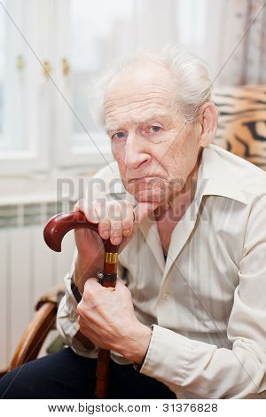 sad lonely old man sitting in an armchair with his cane stock photo
