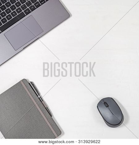 Workplace Freelancer. Grey Modern Laptop, Metallic Pen, Copybook And Computer Mouse On Light Backgro