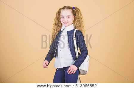 Schoolgirl with small leather backpack. Carry bag comfortable. Stylish mini backpack. Learn how fit backpack correctly. Girl little fashionable cutie carry backpack. Popular useful fashion accessory stock photo
