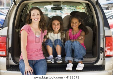 Woman and children sat relaxing in boot of car stock photo