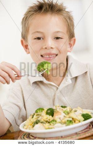 Portrait of young boy looking fed up with plate of healthy food stock photo