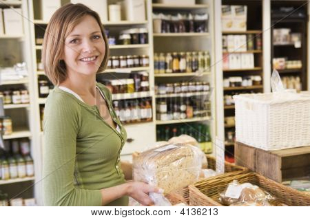 Woman working in local shop handling produce stock photo