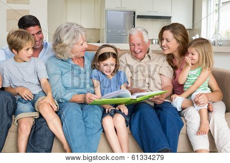 Multigeneration family reading storybook in living room stock photo