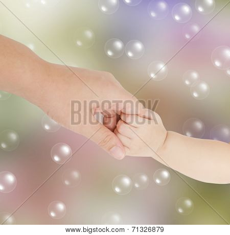 Baby Hand Holding Her Mother Finger over colorful background stock photo