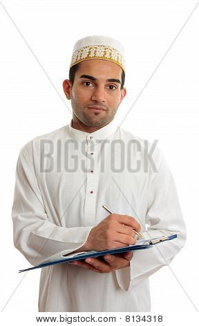 Arab mixed race business man wearing traditional middle eastern attire and topi gold embroidered hat. He is holding a clipboard folder and writing. White background. stock photo