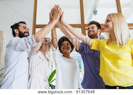 business, startup, gesture, people and teamwork concept - happy creative team making high five in of