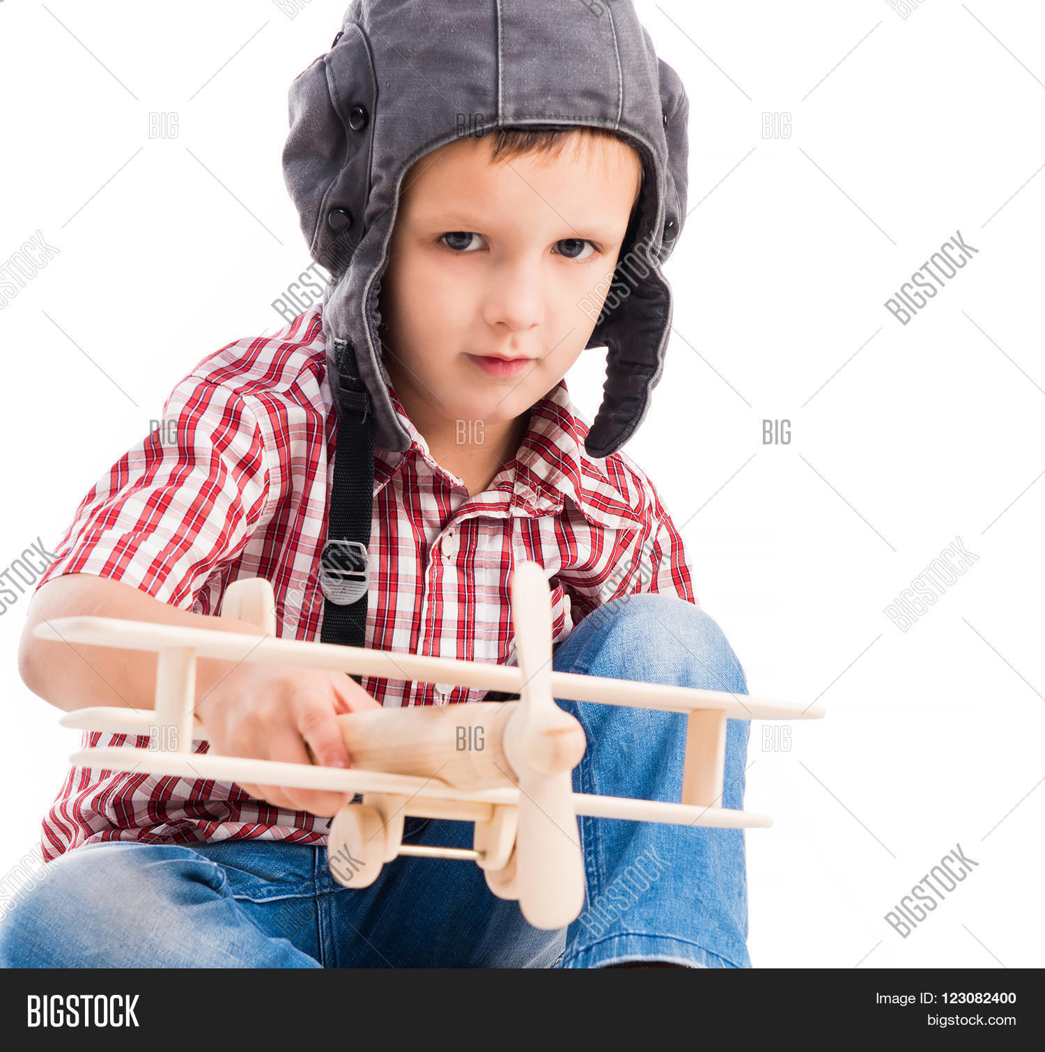 air,airman,airplane,aspirations,aviation,aviator,background,blue,boy,child,childhood,cute,dream,face,fantasy,flight,floor,fly,fun,guy,hand,handsome,happy,hat,helmet,imagination,isolated,kid,little,male,on,pilot,plane,play,sitting,smile,the,toy,toy-plane,white,wings,wooden,young