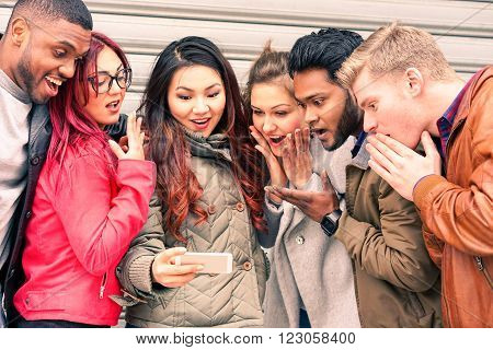 Multiracial group of young friends surprised face looking mobile phone new miracles technology - Mixed race best friendship and astonished facial expression concept - Main focus Indian man at right