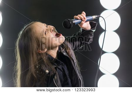 Young rock star with mic on stage with stagelights behind her stock photo