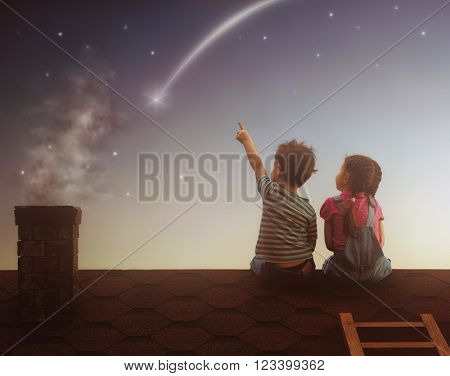 Two cute children sit on the roof and look at the stars. Boy and girl make a wish by seeing a shooti