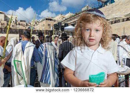 Cute little boy with long blond curls and blue eyes in blue skullcap. He stands at Western Wall of Temple. The Jewish holiday of Sukkot stock photo