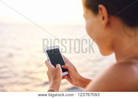 Smartphone woman texting on social media app looking at display screen for sms reading on ocean back