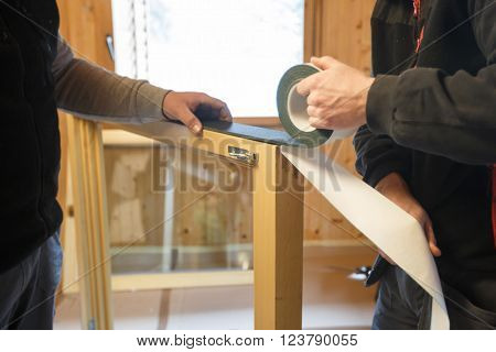 Workers applying a RAL self-adhesive insulating tape to install new three pane wooden windows in a wooden house. Home renovation sustainable living energy efficiency concept. stock photo