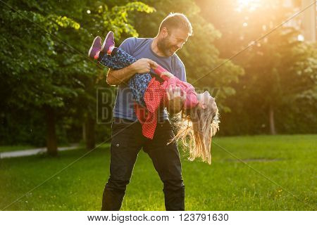 Devoted father spinning his daughter in circles bonding playing having fun in nature on a bright sunny day. Parenthood lifestyle parenting childhood and family life concept.