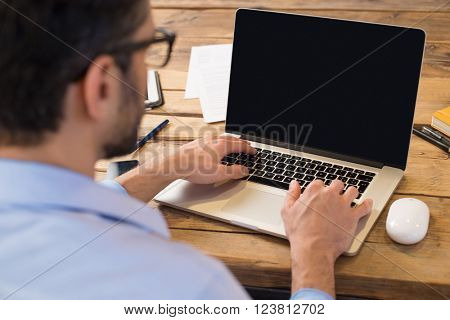 Back view of businessman sitting in front of laptop screen. Man typing on a modern laptop in an offi