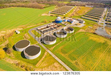 Aerial view to biogas plant from pig farm in green fields. Renewable energy from biomass. Modern agr