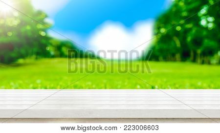 Empty white wood table top with blur green grass field natural park in sunny day.Mock up for display of product,Banner or header for advertise on social media,Spring and Summer background. stock photo
